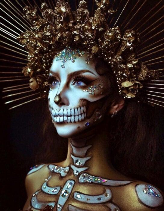 Maquillajemoderno de Catrina de Día de Muertos; mujer de ojos azules con corona dorada y piedras swarovski en el rostro