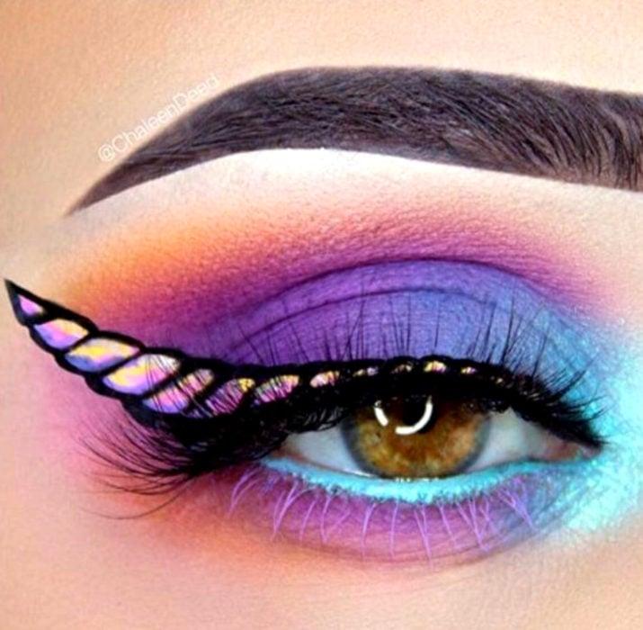 Maquillaje de ojos de Halloween; sombra morada, azul y rosa, con delineado cat eye de cuerno de unicornio