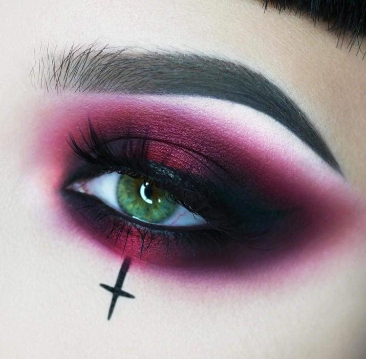 Maquillaje de ojos de Halloween; sombra rojo vino con negro y una cruz, vampiro