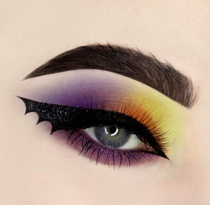 Maquillaje de ojos de Halloween; sombra morada, amarilla y anaranjada con delineado en forma de ala de murciélago