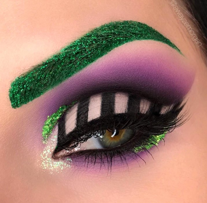 Maquillaje de ojos de Halloween; sombra morada, blanca con rayas negras y ceja verde de Beetlejuice