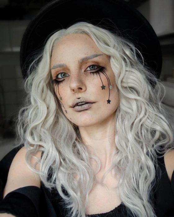Chica con cabello blanco y maquillaje a estrellas negras