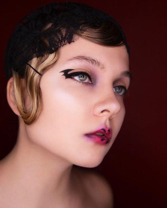 Chica con pequeñso murciélagos dibujados en los labios