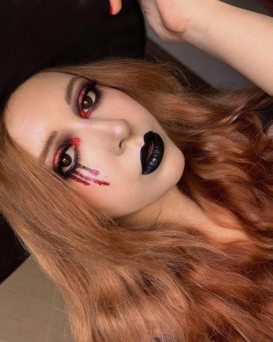 Chica con maquillaje en forma de lagrimas en tono rojo
