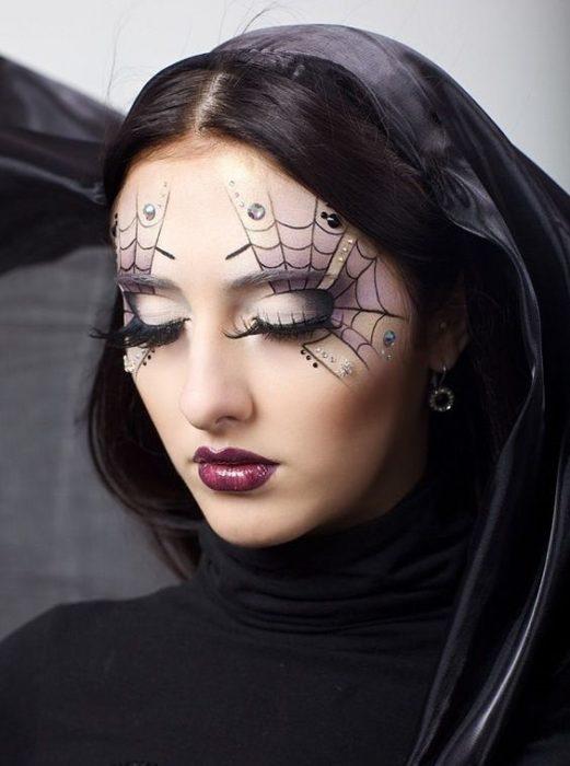 Chica mostrando su maquillaje con telarañas en los ojos