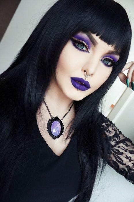 Chica llevando maquillaje inspirado en bruja con tonos morados