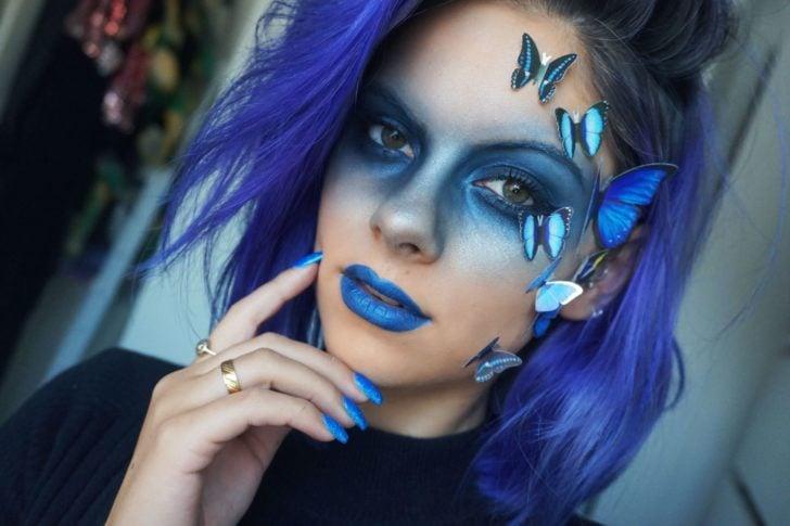Chica maquillada en tonos azul y morado simulando ser una bruja