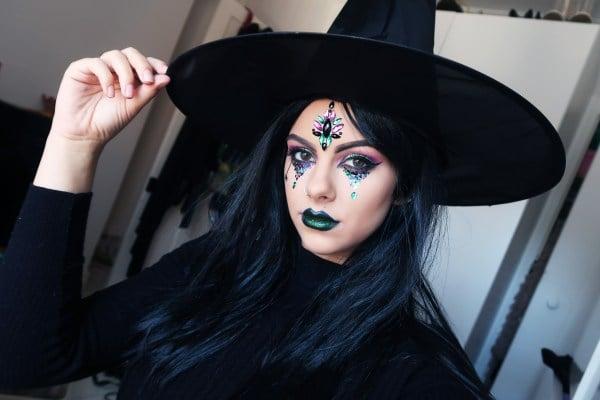 Chica con pedreria pegada e el rostro simulando una bruja