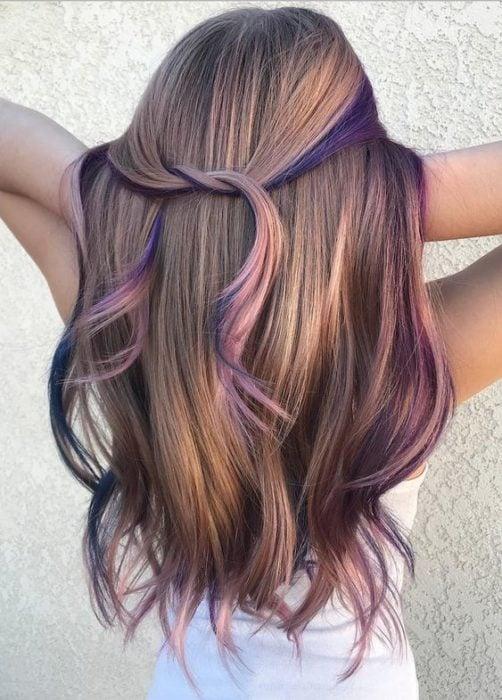 Chica jugando con su cabello castaño con mechas rosa pastel
