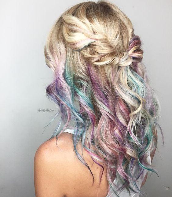 Chica con cabello rubio con mechas en tonos pastel rosa, verde y azul