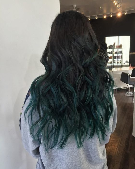 Chica de espaldas mostrando sus mechas de color verde