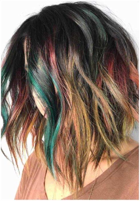 Chica de perfil mostrando su cabello con mechas de colores verde, vino y amarillo