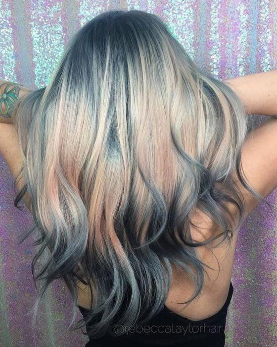 Chica ocn cabello rubio mostrando sus mechas en azul grisaseo
