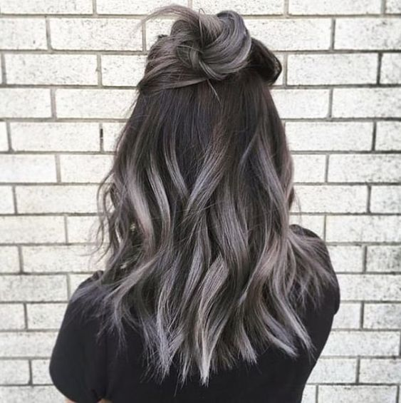 Chica mostrando su cabello con mechas rubias y cenizo