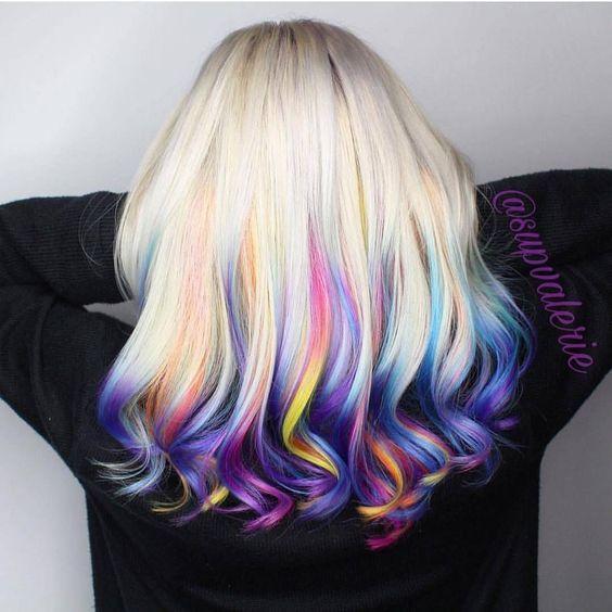 Chica de espaldas mostrando su cabello con mechas de colores estilo arcoíris