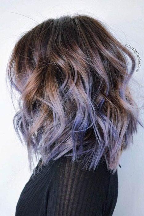 Chica con cabello castaño mostrando sus mechas en tono lila