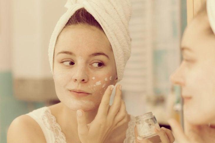 Mujer aplicándose crema en el rostro luego de una ducha