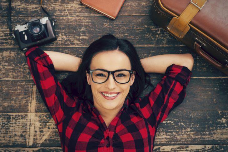 Mujer con camisa de cuadros rojo y negro, con lentes