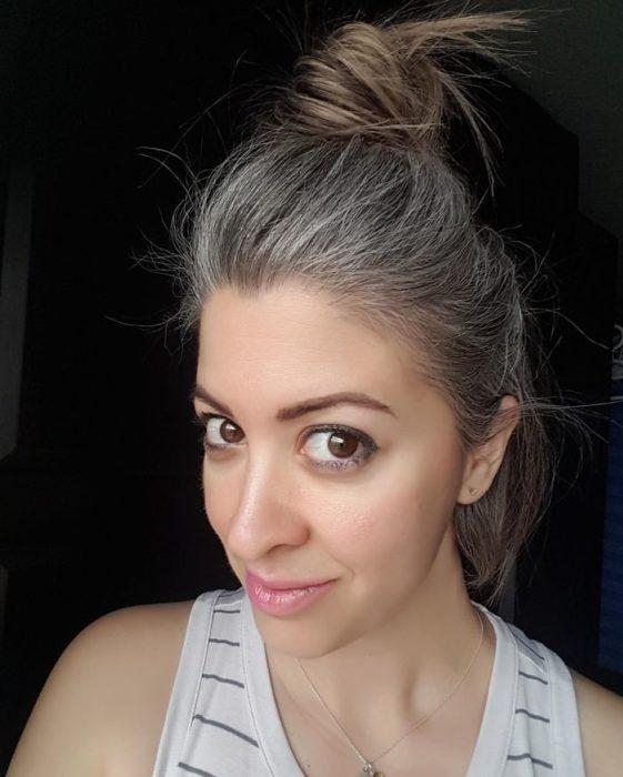 Chica con el cabello atado en un chongo mostrando sus canas