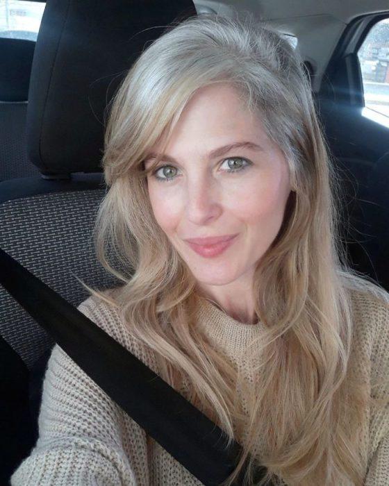 Chica mostrando sus canas mientras se toma una foto en su automóvil