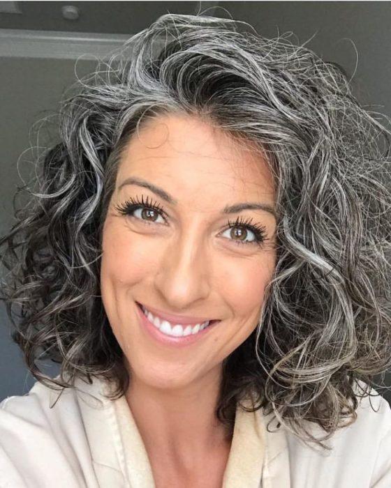 Chica de cabello corto con lentes mostrando su cabello cubierto con canas