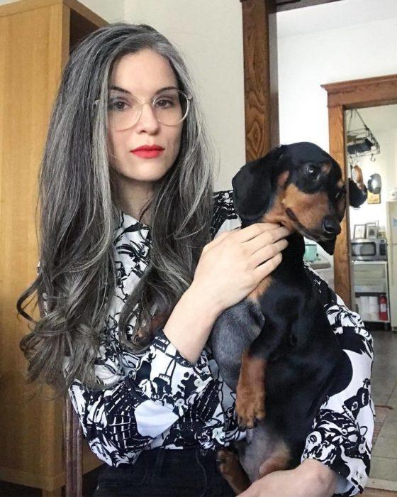 Chica de cabello largo y canoso parada frente a una cámara tomandose una foto mientras está con su perro