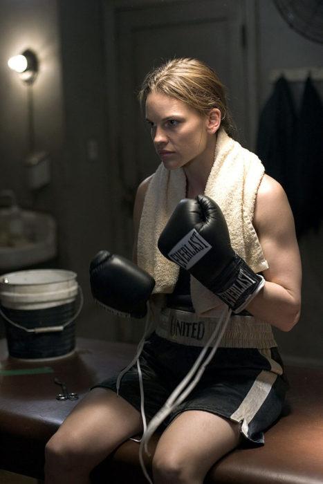 una mujer con guantes y ropa deportiva y una toalla alrededor del cuello sentada pensativa