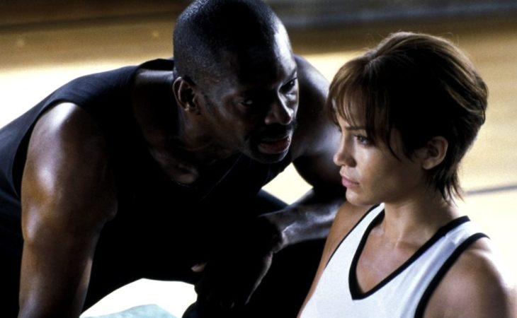 una mujer en ropa deportiva piensa mientras un hombre le dice algo al oído