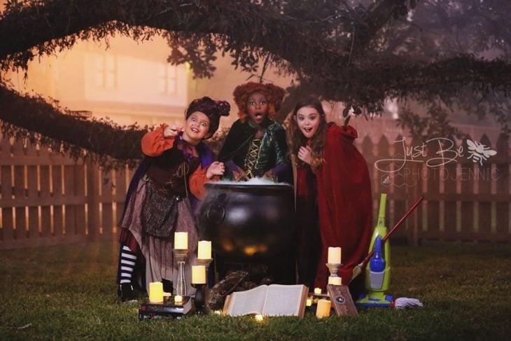 Niñas disfrazadas de la película de brujas Hocus Pocus para Halloween; Winifred, Sarah y Mary Sanderson; caldero humeante