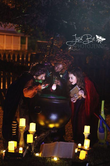 Niñas disfrazadas de la película de brujas Hocus Pocus para Halloween; Winifred, Sarah y Mary Sanderson; caldero