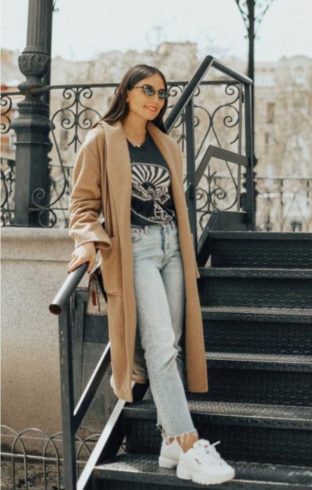 Chica usando unos pantalones de mezclilla con blusa negra saco largo de color café y tenis fila de color blanco