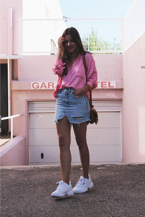 Chica usando una falda de mezclilla, blusa de color rsa con unos tenis fila de color blanco
