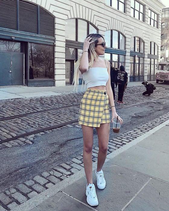 Chica parada en medio de la calle usando una falda de color amarillo con cuadros y top blanco con tenis fila de color blanco
