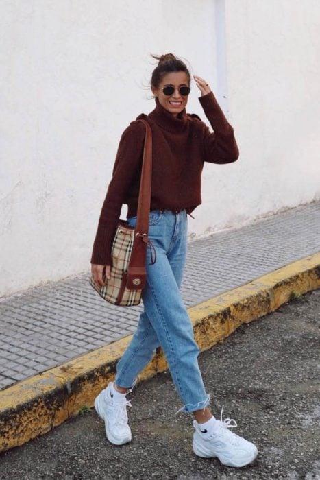 Chica usando unos jeans, suéter de color café y tenis fila de color blanco