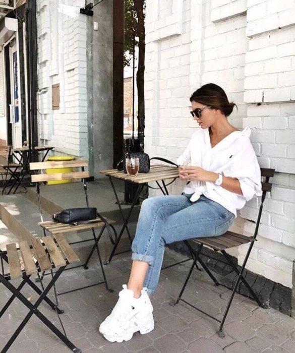 Chica sentada en un café mientras usa unos pantalones de mezclilla, blusa blanca y tenis fila de color blanco