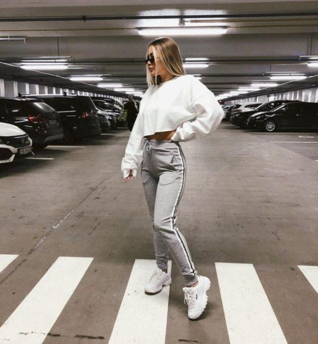 Chica parada en medio de un estacionamiento usando un pantalón de color girs, suéter blanco y tenis fila blancos