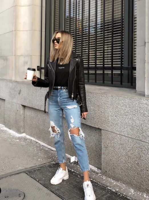 Chica parada en medio de la calle sosteniendo un café mientras usa jeans desgarrados, chaqueta y blusa negra y tenis fila de color blanco
