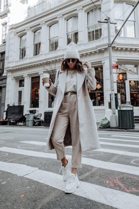 Chica usando un conjunto de color beige con abrigo y gorro con unos tenis fila de color blanco