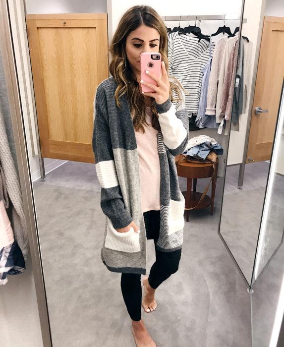Oversized cardigan; mujer tomándose una selfie frente al espejo, con suéter holgado color gris y blanco