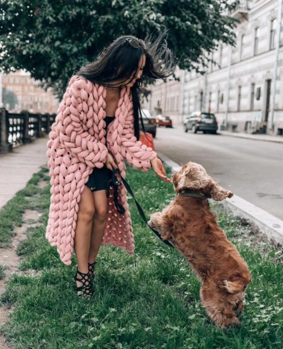 Oversized cardigan; chica con suéter holgado de crochet grueso color rosa, con su perro cocker spaniel café