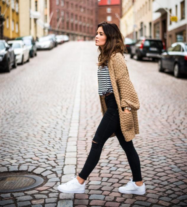 Oversized cardigan; chica caminando en calle empedrada con suéter holgado tejido color café, con pantalones entubados y tenis blancos