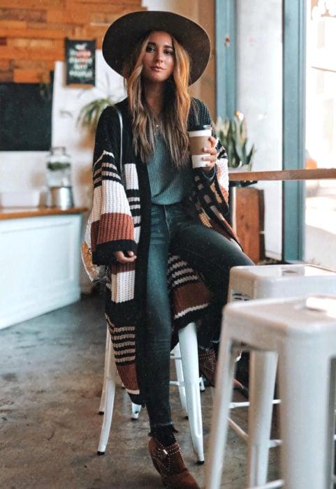 Oversized cardigan; mujer con estilo boho en un café, chica con cabello rubio, sobrero de ala ancha, botines, suéter holgado y largo