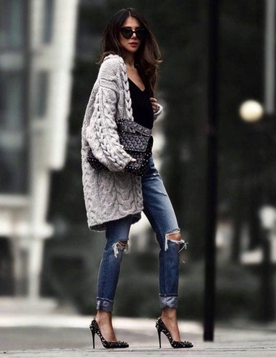 Oversized cardigan; mujer de cabello largo y castaño, con lentes de sol en forma de corazón negros, con pantalones rasgados de la rodilla, zapatillas stiletto y suéter holgado y largo, tejido color gris,bolsa de mano negra con estoperoles