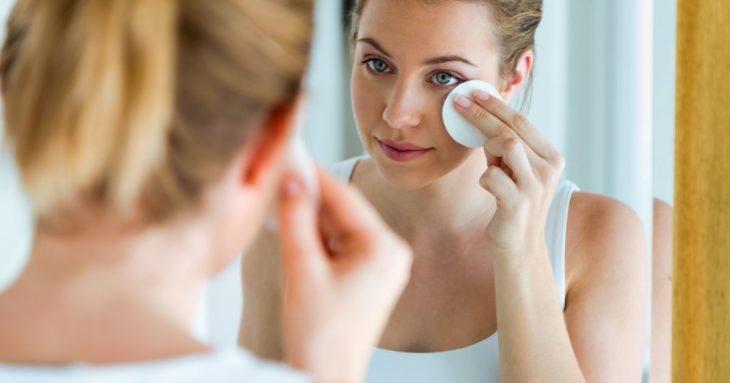 Chica frente un espejo desmaquillando su rostro con una toallita de algodón