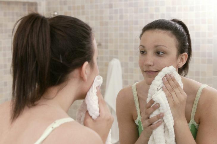 Chica frente al espejo secando su cara con una toalla