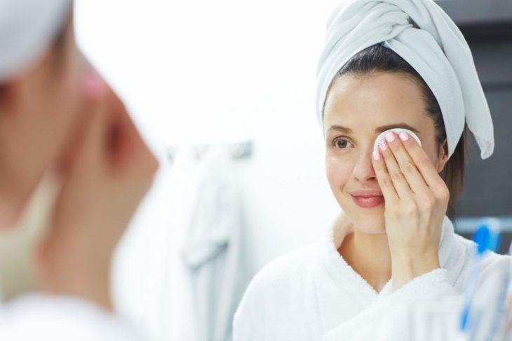 Chica frente al espejo usando una bata de baño y una toalla en la cabeza mientras desmaquilla sus ojos con una almohadilla de algodón