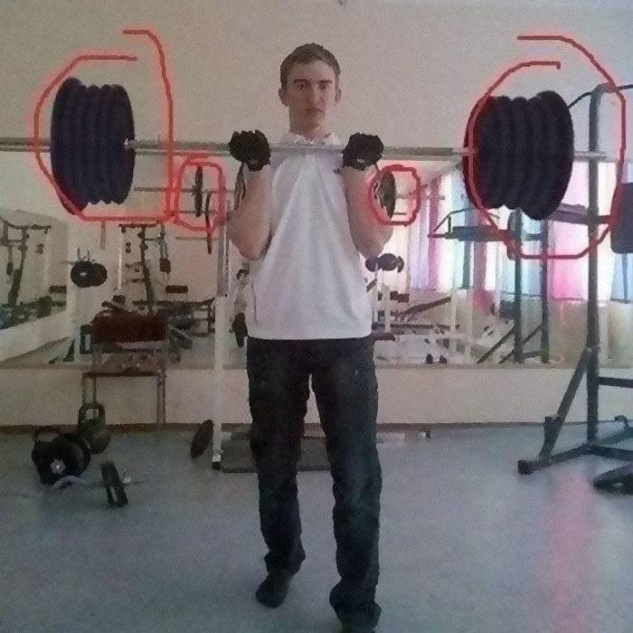Chico en el gimnasio cargando pesas con varios kilos y atrás en el reflejo cargando poco peso