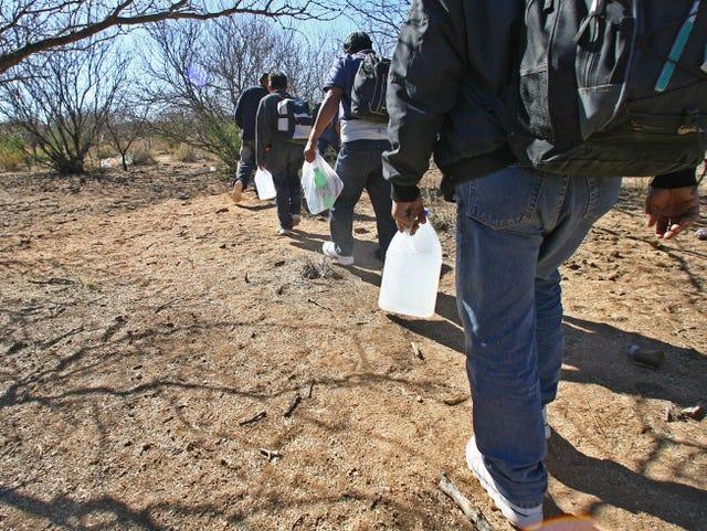varios hombres caminan por una zona desértica con galones de agua en sus manos