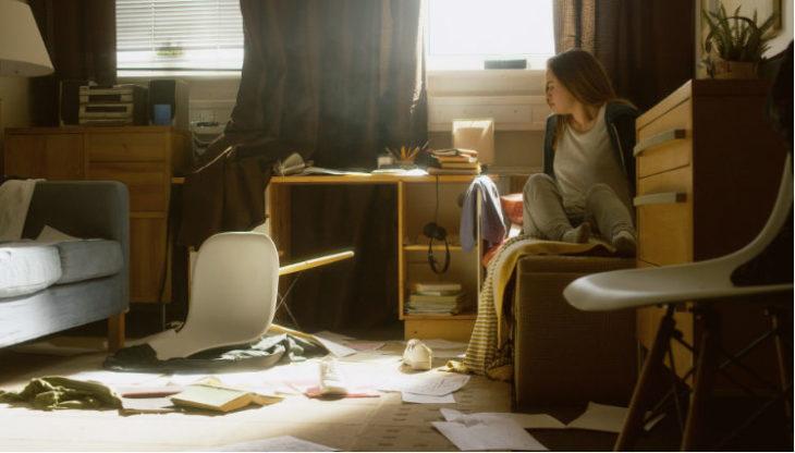Chica asustada dentro de una habitación desordenada, escena de la serie Lo que vi