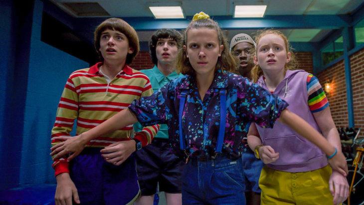 Grupo de niños asustados, usando ropa de los 80, escena de la serie Stranger Things